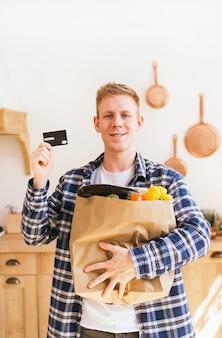 O cara está segurando um pacote de mantimentos e um cartão de crédito em casa na cozinha de compras online