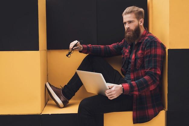 O cara está sentado em móveis modernos. ele está na loja.