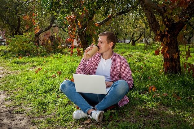 O cara está sentado na grama verde do parque com uma xícara de café e trabalhando em um laptop. trabalho freelance ao ar livre. trabalhando fora do escritório devido à pandemia de covid 19