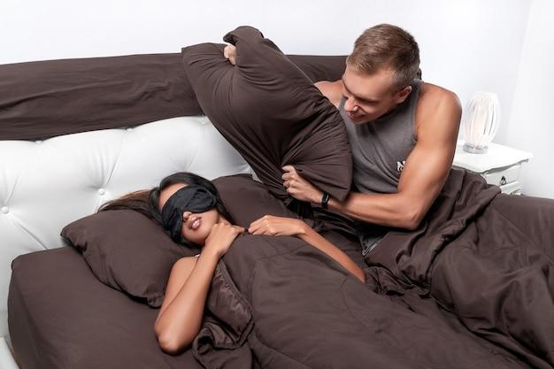 O cara está tentando cobrir a garota com um travesseiro, enquanto sua namorada dorme docemente,
