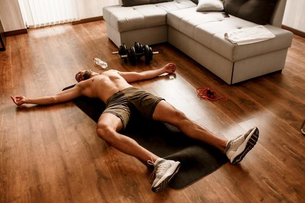 O cara está treinando em casa e muito cansado após o treino. ele está deitado em um tapete de ioga suado e sem camiseta