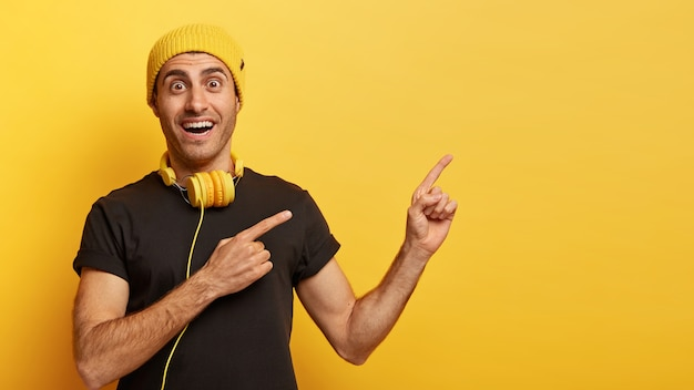 O cara feliz e moderno aponta para o lado com os dois dedos da frente e anuncia espaço de cópia para o seu conteúdo de publicidade