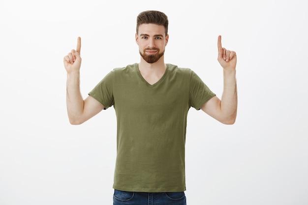 O cara garantiu que você precisa verificar o produto, apontando com o dedo indicador levantado para o espaço da cópia com um sorriso confiante, parecendo rígido e seguro de si, encorajando experimente sobre uma parede branca