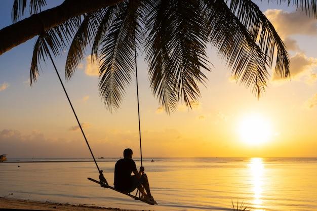 O cara gosta de pôr do sol andando em um balanço na praia tropical. silhuetas de um cara em um balanço pendurado em uma palmeira, assistindo o pôr do sol na água.