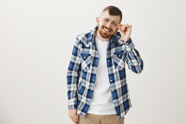 O cara hipster estiloso tem problemas de visão, coloca óculos e aperta os olhos, não consegue ver
