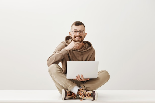 O cara hipster sentado com as pernas cruzadas com o laptop e sorrindo satisfeito