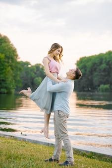 O cara levantou as mãos em volta da cintura da namorada, olhando para ela, eles sorriam e felizes