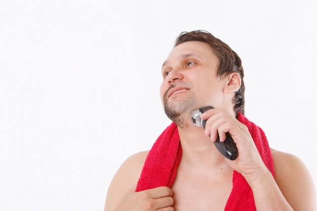 O cara limpa a barba com um barbeador elétrico