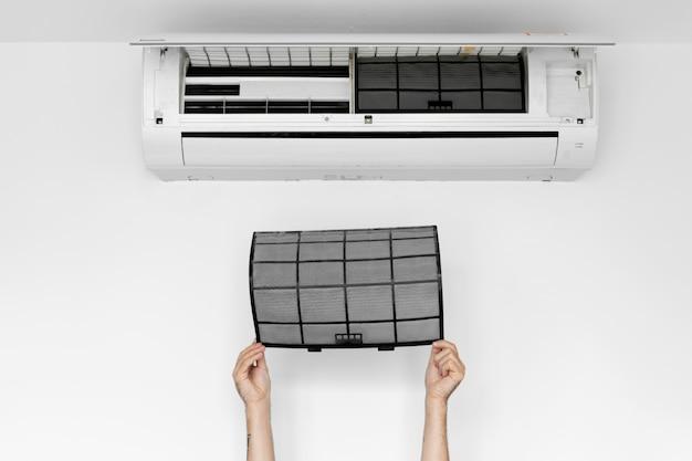 O cara limpa o filtro do ar condicionado doméstico da poeira.