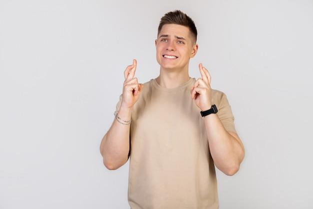 O cara mantém os dedos cruzados com uma expressão preocupada