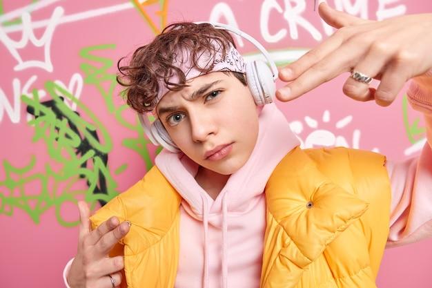 O cara moderno e moderno faz seu gesto parecer legal enquanto ouve música rap com fones de ouvido sem fio, tem cabelo encaracolado, usa um capuz da moda e colete amarelo posa contra uma parede de grafite