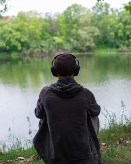 O cara na margem do rio ouvindo música. longe da cidade circundante. ouça fones de ouvido com música