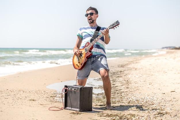 O cara na praia com instrumentos musicais