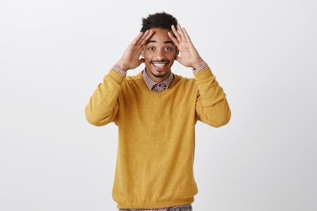 O cara não esperava ver um amigo de longa data na festa de aniversário. estudante do sexo masculino de pele escura feliz e emocionado com penteado afro, segurando as palmas das mãos na testa e sorrindo amplamente, sendo agradavelmente surpreendido