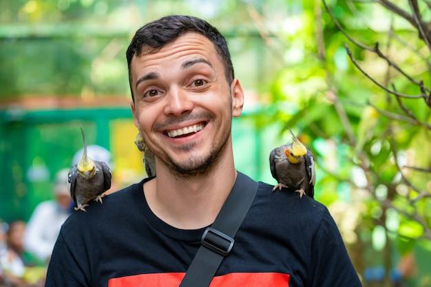 O cara no parque de pássaros se comunica com papagaios. papagaios domesticados imploram por comida aos turistas.