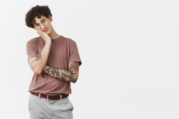 O cara odeia ficar em casa sem fazer nada. retrato de homem jovem urbano, bonito e elegante entediado com bigode, braço tatuado e cabelo encaracolado apoiado na palma da mão indiferente e sombrio