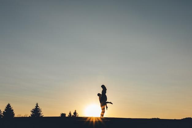 O cara pegou a garota nos braços ao pôr do sol