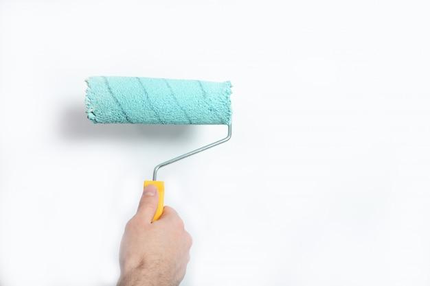 O cara pinta a parede de azul com um rolo de construção