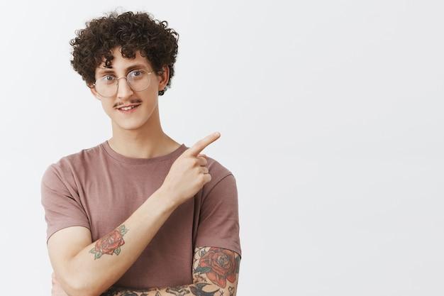 O cara recomenda uma boa visita à loja. homem adulto charmoso e amigável com bigode cacheado e tatuagens sorrindo amplamente em óculos da moda apontando para o canto superior direito no espaço da cópia