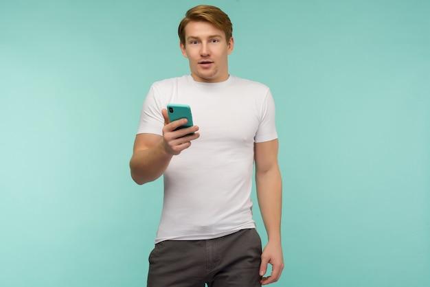 O cara ruivo de esportes surpreso recebeu notícias chocantes em um smartphone em um espaço azul.