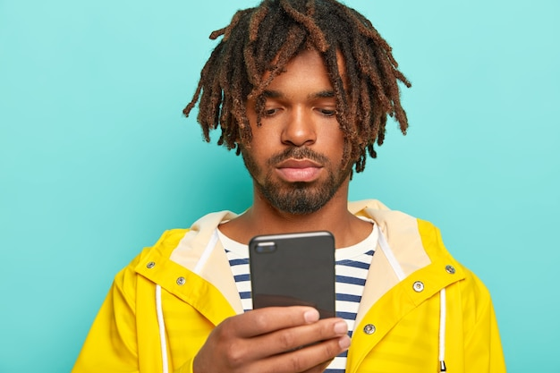 O cara sério usa celular moderno, navega na página da internet, faz pagamentos online, usa macacão listrado e capa de chuva amarela impermeável