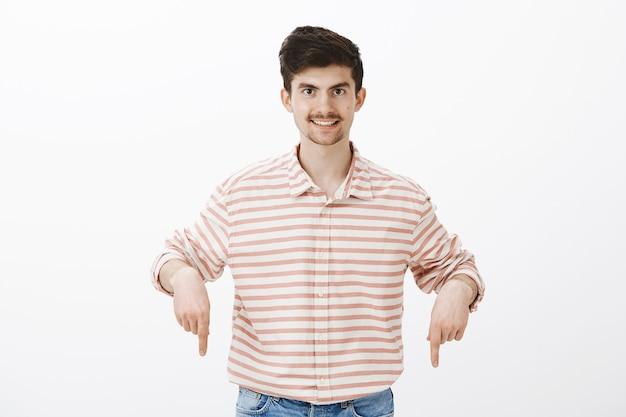 O cara sugere a melhor oferta. retrato de um homem barbudo intrigado e satisfeito com uma camisa listrada, apontando para baixo