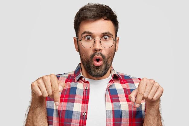 O cara surpreso com expressão atordoada aponta para baixo, tem os olhos esbugalhados, encara com descrença, usa camisa xadrez brilhante, fica encostado na parede branca. belo jovem barbudo dentro de casa