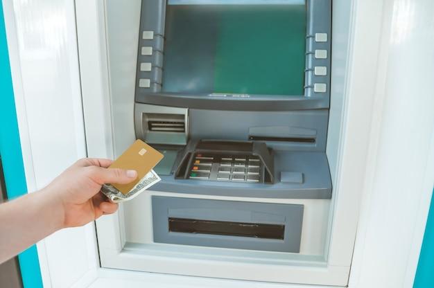 O cara tem dinheiro e um cartão do banco na mão na frente de um caixa eletrônico.