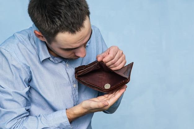 O cara tira o último rublo de uma bolsa vazia. pobreza e desemprego. homem sem dinheiro. empresário segurando uma carteira vazia.