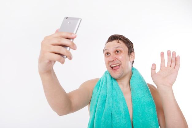 O cara tira uma selfie após os procedimentos matinais. um homem olha para a câmera do telefone. rosto bem barbeado. toalha azul em volta do pescoço. homem e tecnologias modernas. a conversa via link de vídeo