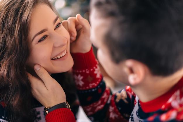 O cara toca gentilmente o rosto da garota e ela sorri fofo. fechar-se. suéteres de inverno.
