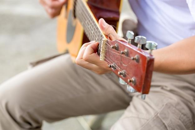 O cara tocando violão, ao ar livre, calças cargo