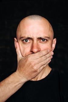O careca cobre a boca com a mão. o medo é o medo de falar. um homem com uma camiseta preta sobre um fundo preto cobre a boca com a mão.