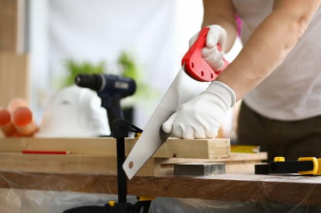 O carpinteiro com luvas usa a parte fixa de serra transversal