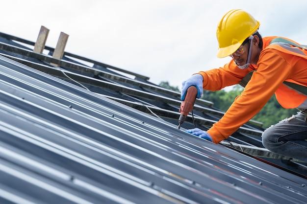 O carpinteiro da construção usa inspeção uniforme de segurança e instala trabalhos de cobertura metálica para o telhado industrial.