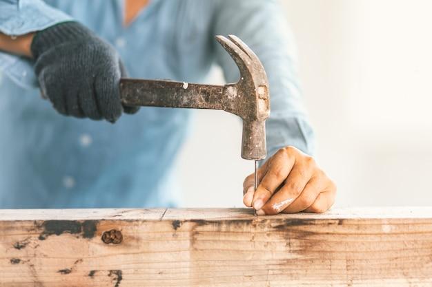 O carpinteiro está consertando a casa.