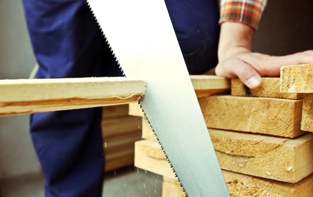 O carpinteiro está cortando a prancha de madeira pela serra