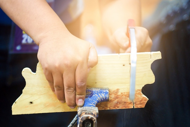 O carpinteiro está usando uma serra para cortar madeira. um carpinteiro, um homem, fez uma serra de madeira