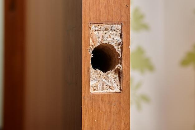O carpinteiro fez um orifício para o trinco da fechadura da porta em folha de aglomerado e uma moldura retangular oca com cinzel para afundar a chapa