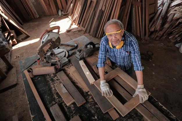 O carpinteiro masculino usa uma lixa para polir a madeira.