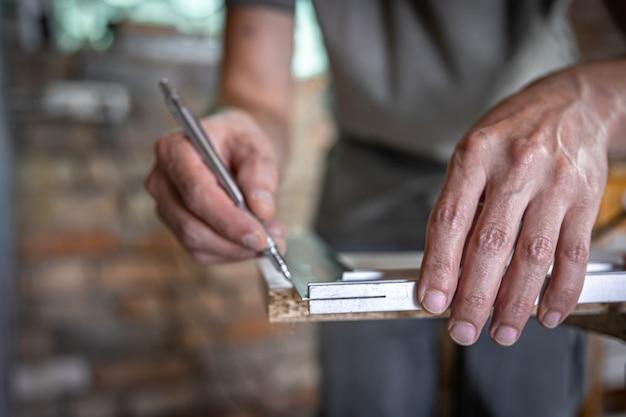O carpinteiro mede a madeira com uma ferramenta angular e faz anotações.