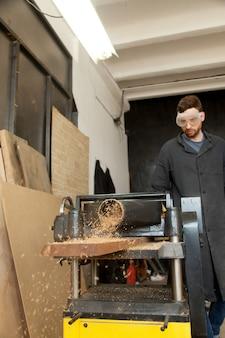 O carpinteiro reduz a espessura da placa na máquina de plaina
