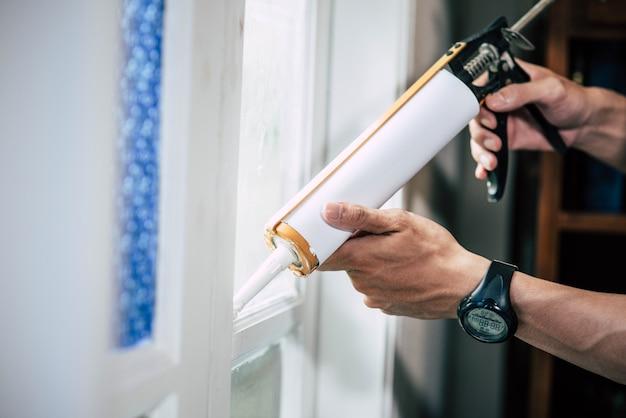 O carpinteiro segura a cola e gruda na janela.