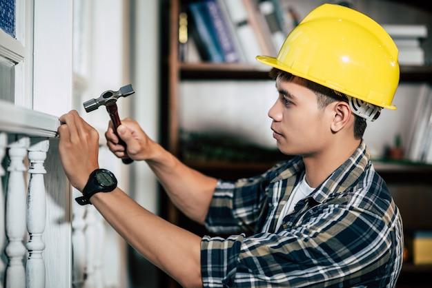 O carpinteiro segura o martelo e os pregos.