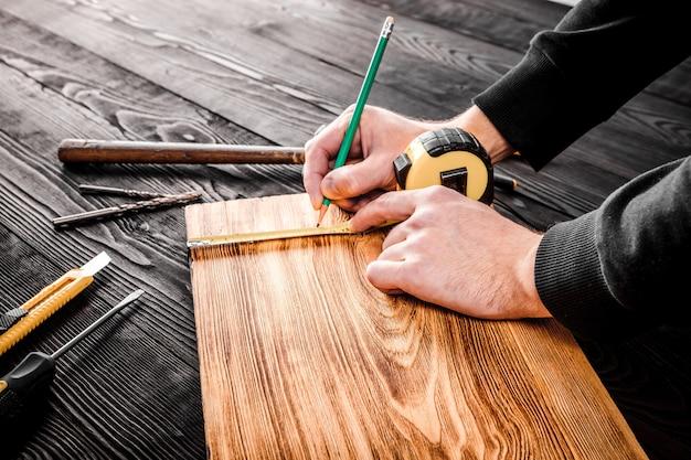 O carpinteiro trabalha com madeira em seu espaço de trabalho