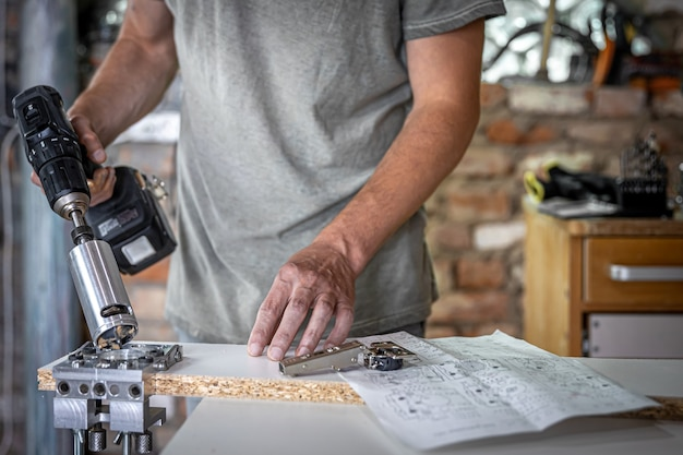 O carpinteiro trabalha com uma ferramenta profissional de perfuração de precisão.