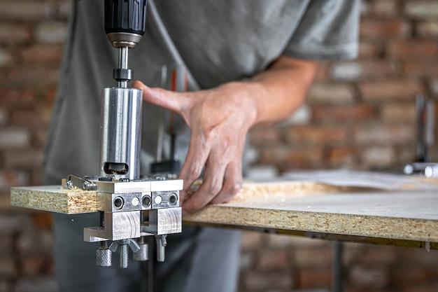O carpinteiro trabalha como ferramenta profissional para furar madeira.