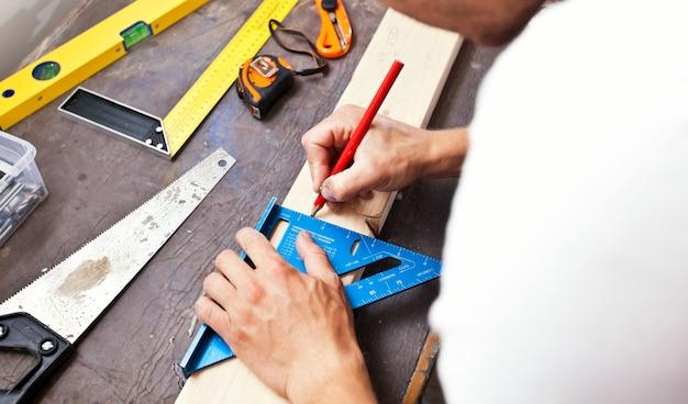 O carpinteiro traça a linha a lápis na prancha de madeira