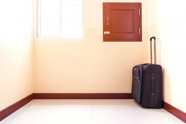 O carrinho de bagagem foi colocado no canto da sala.