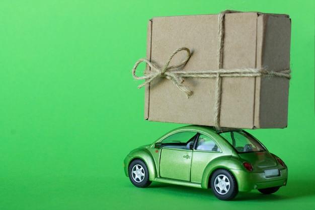 O carrinho de brinquedo verde entrega um pacote em uma caixa de papelão artesanal sobre um fundo verde pastel. entrega de mercadorias, presentes ou conceito de doação.